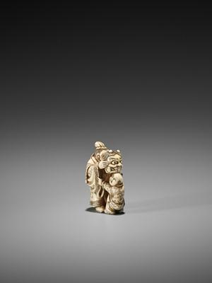 Lot 74-HIDEMASA: AN IVORY NETSUKE OF A MAN TEASING A KARAKO WITH AN ONI MASK