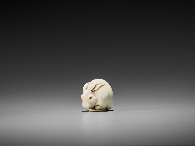 91 - UEDA KOHOSAI: A SUPERB IVORY NETSUKE OF A CROUCHING HARE WITH AMBER EYES