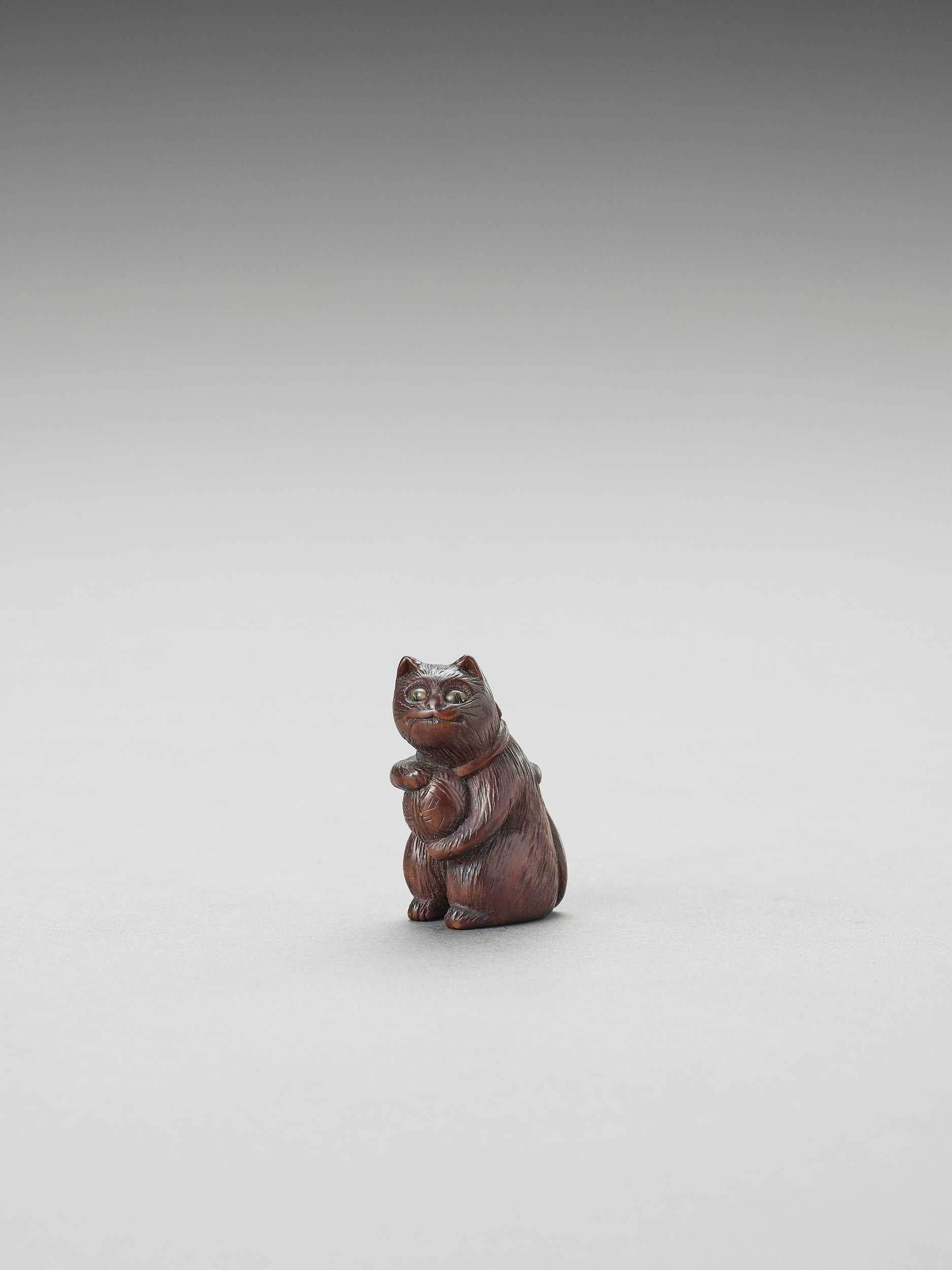 A CHARMING TOKYO SCHOOL WOOD NETSUKE OF A CAT WITH A BALL