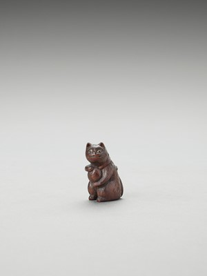 Lot 323 - A CHARMING TOKYO SCHOOL WOOD NETSUKE OF A CAT WITH A BALL
