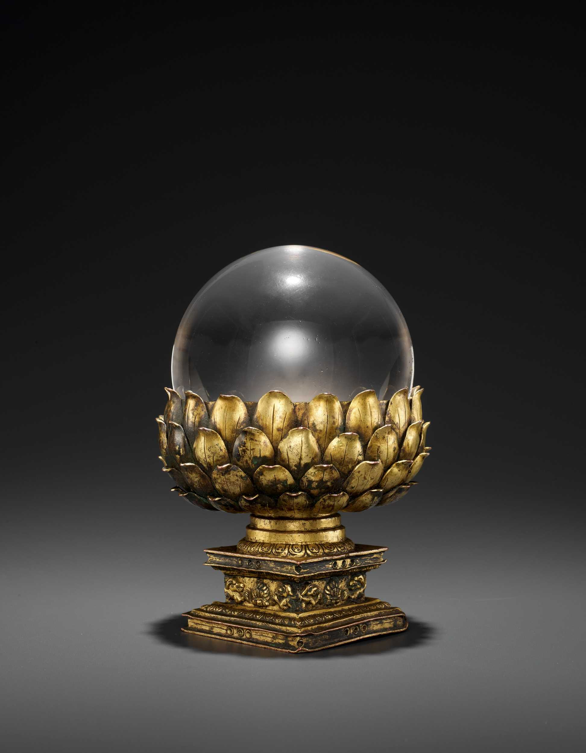 Lot 34 - A ROCK CRYSTAL SPHERE WITH A GILT BRONZE LOTUS BASE, QING DYNASTY