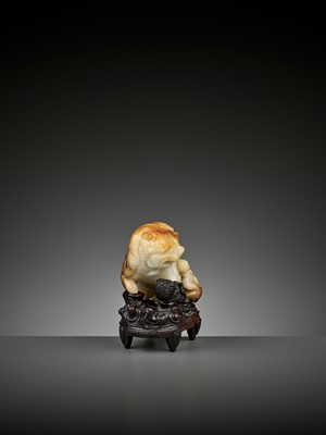 Lot 67 - A RUSSET AND WHITE JADE 'BUDDHIST LION' WATER POT AND COVER WITH MATCHING HARDWOOD BASE, LATE MING TO EARLY QING
