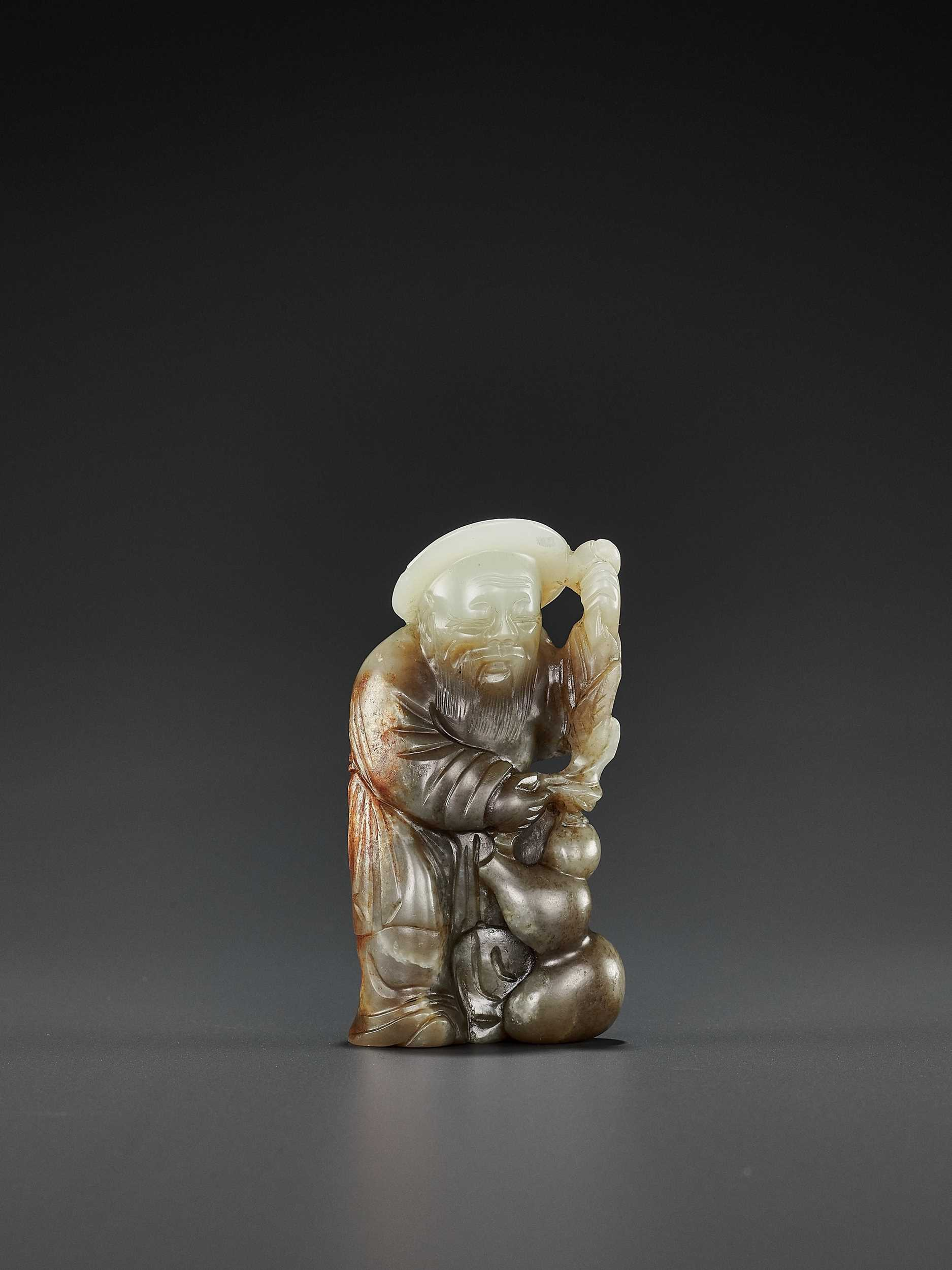 Lot 66 - A PALE CELADON, GRAY AND RUSSET JADE FIGURE OF DONGFANG SHUO, QING DYNASTY