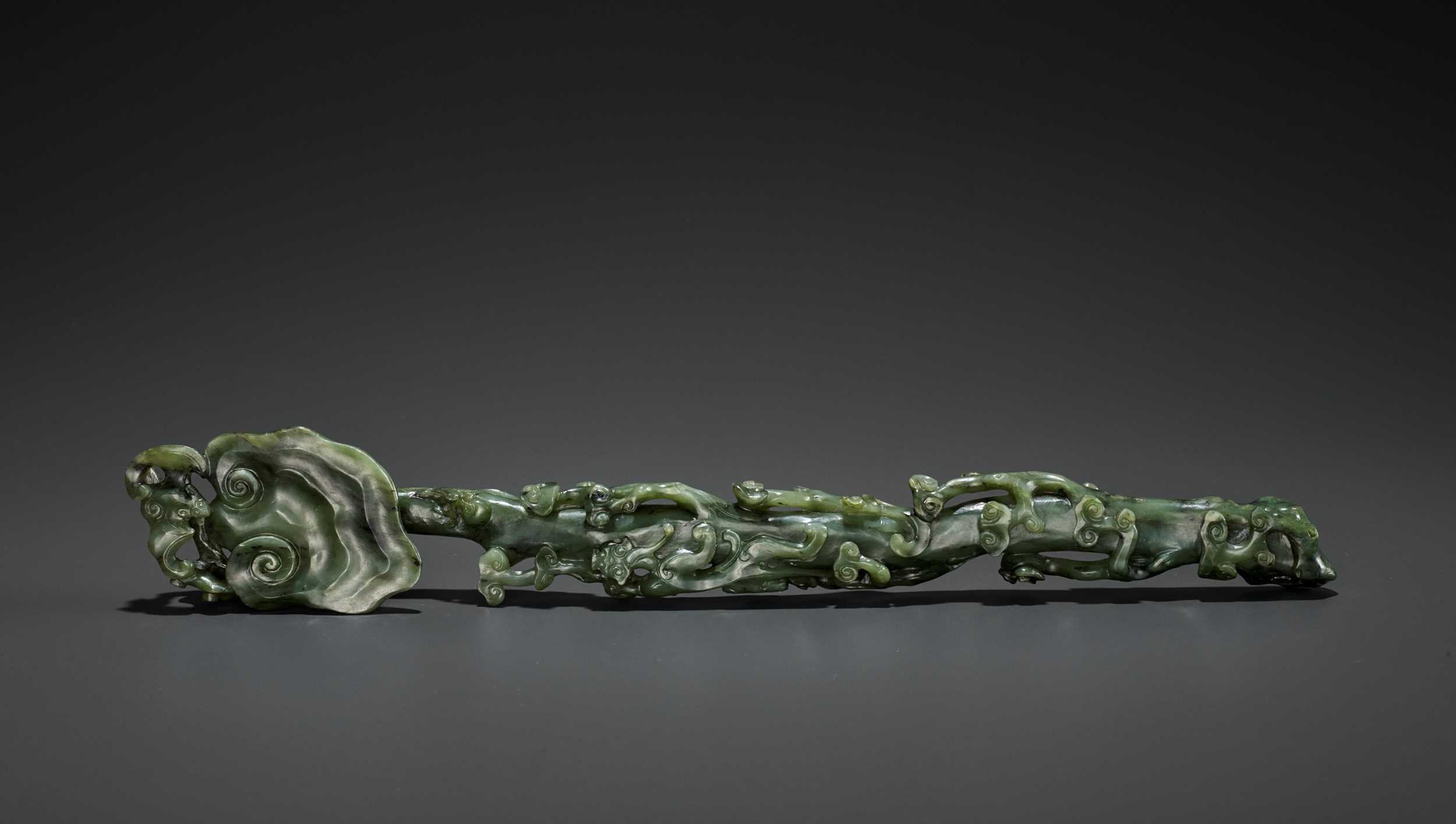 Lot 70 - A SPINACH-GREEN JADE RUYI SCEPTER, MID-QING