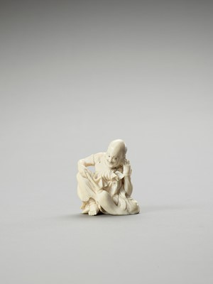 Lot 241 - AN IVORY OKIMONO OF A RAKAN CLEANING HIS EAR