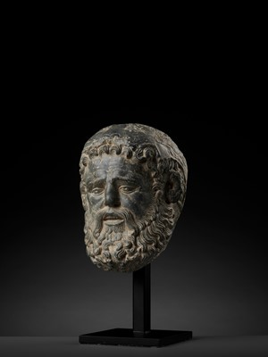 Lot 695 - A LIFE-SIZED HEAVY GRAY SCHIST HEAD OF HERACLES, GANDHARA, 4TH-5TH CENTURY