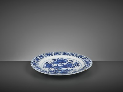 Lot 321 - A LARGE BLUE AND WHITE 'PRUNUS AND BUTTERFLY' LOBED DISH, KANGXI MARK AND PERIOD