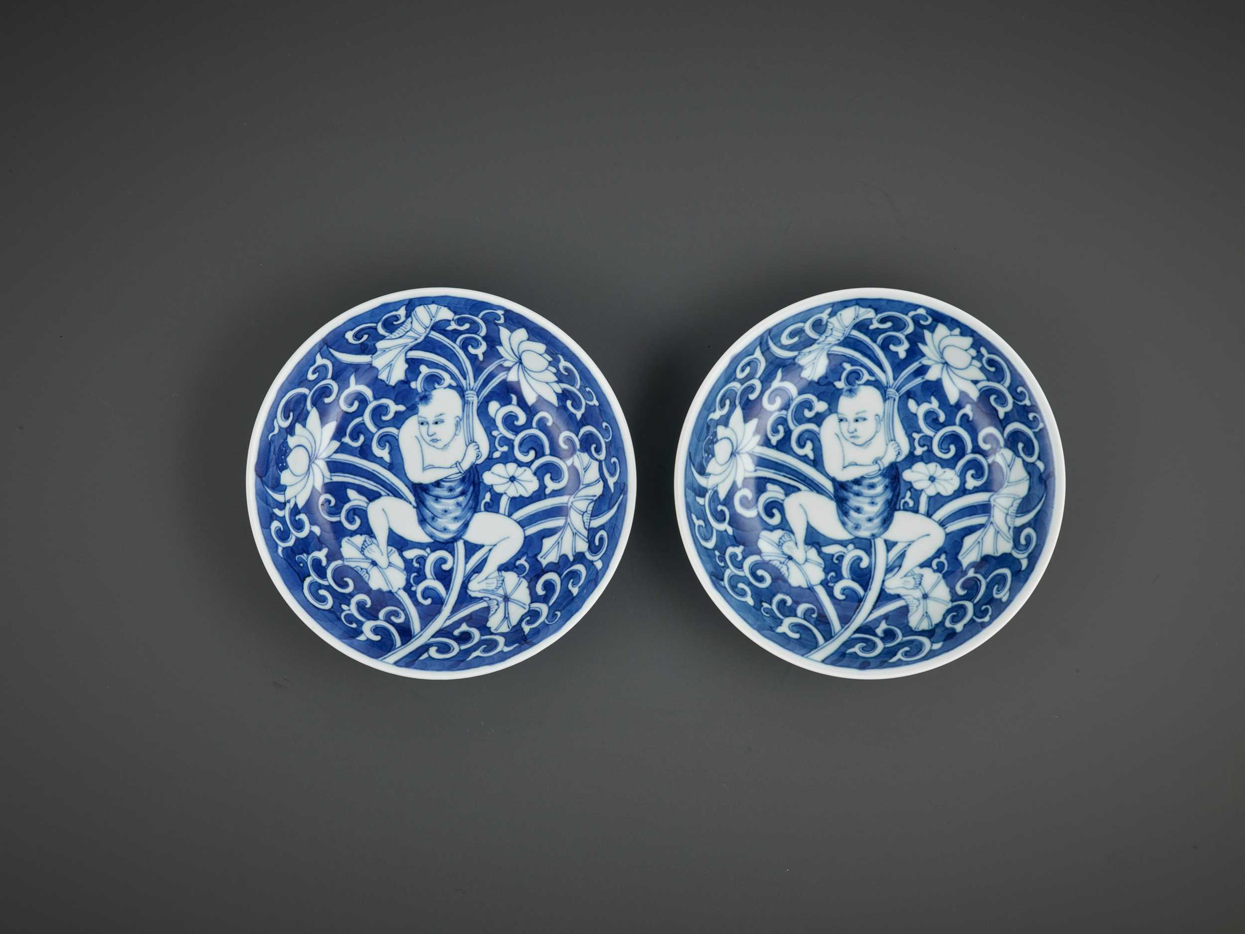 Lot 323 - A NEAR-PAIR OF BLUE AND WHITE 'LOTUS BOY' DISHES, KANGXI PERIOD