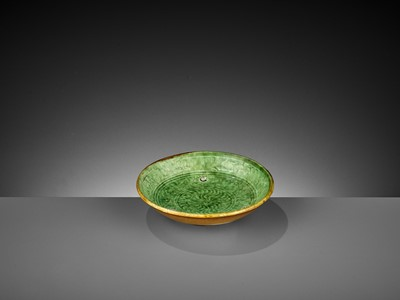 Lot 165 - A MOLDED GREEN AND AMBER-GLAZED POTTERY DISH, LIAO DYNASTY