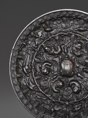 Lot 511 - A BRONZE 'LION AND GRAPEVINE' CIRCULAR MIRROR, TANG DYNASTY