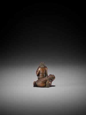 Lot 93 - MASANAO: A RARE WOOD NETSUKE OF GAMA SENNIN SEATED ON THE FROG GOD SEIAJIN