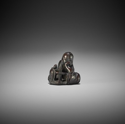 Lot 186 - MINKOKU: A WOOD NETSUKE OF A DRUNKEN SHOJO WITH MINOGAME AND SAKE BARREL