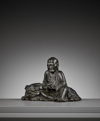 Lot 130 - A LARGE BRONZE OKIMONO OF A RAKAN SEATED ON A SHISHI