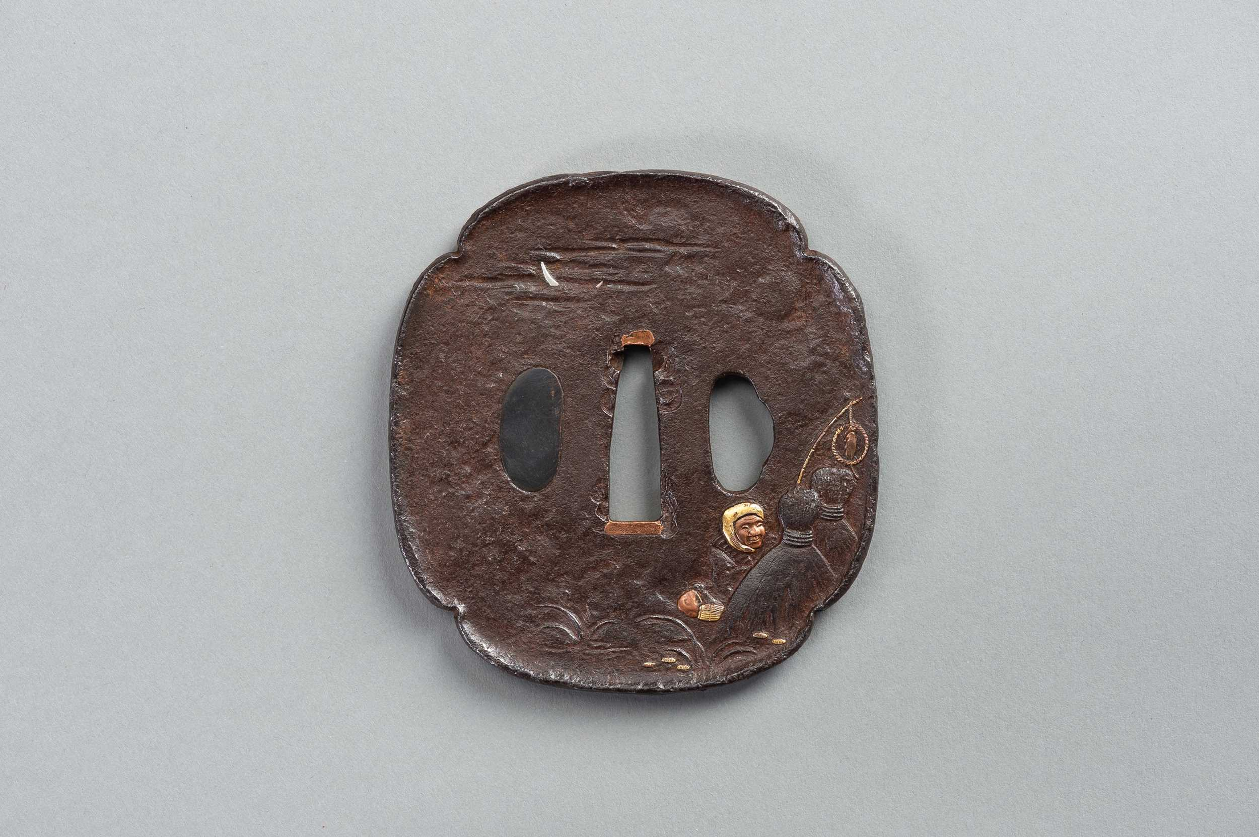 Lot 38 - AN INLAID IRON TSUBA WITH A MAN TRYING TO CATCH A FOX