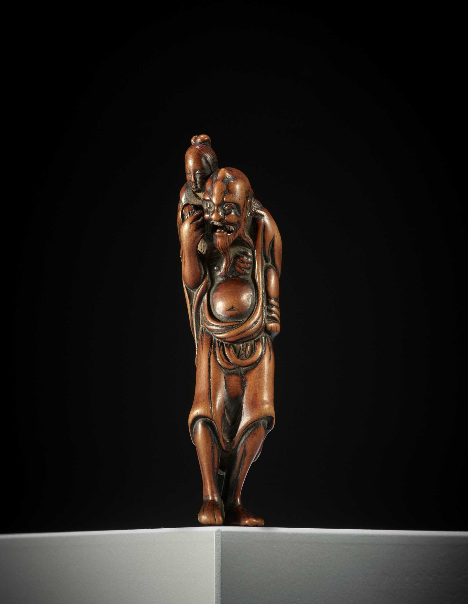 Lot 178 - A TALL EARLY EDO SCHOOL WOOD NETSUKE OF IKKAKU SENNIN CARRYING THE LADY OF BENARES