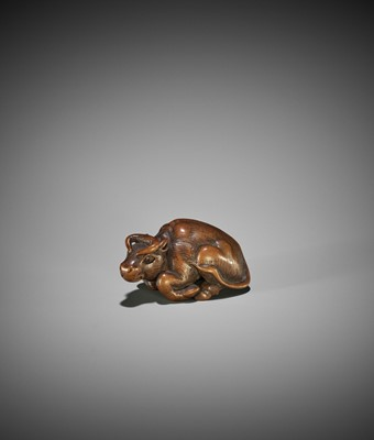 Lot 106 - KOKEI: A WOOD NETSUKE OF A RECUMBENT OX