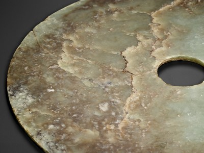 Lot 61 - AN EXCEPTIONALLY LARGE PALE GREEN AND RUSSET JADE BI DISC, EARLY BRONZE AGE