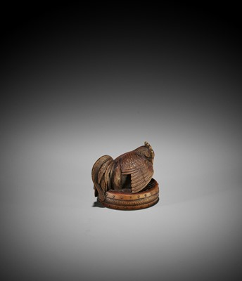 Lot 144 - A NAGOYA SCHOOL WOOD NETSUKE OF A COCKEREL ON A WAR DRUM