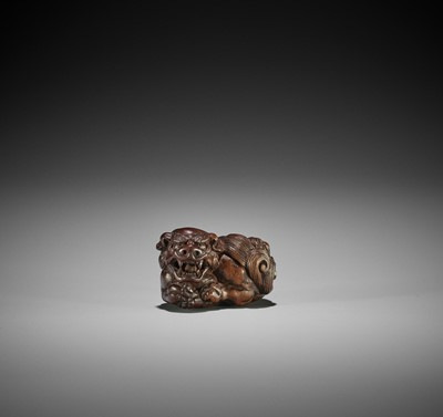 Lot 123 - TAMETAKA: A WOOD NETSUKE OF A RECUMBENT SHISHI ROARING