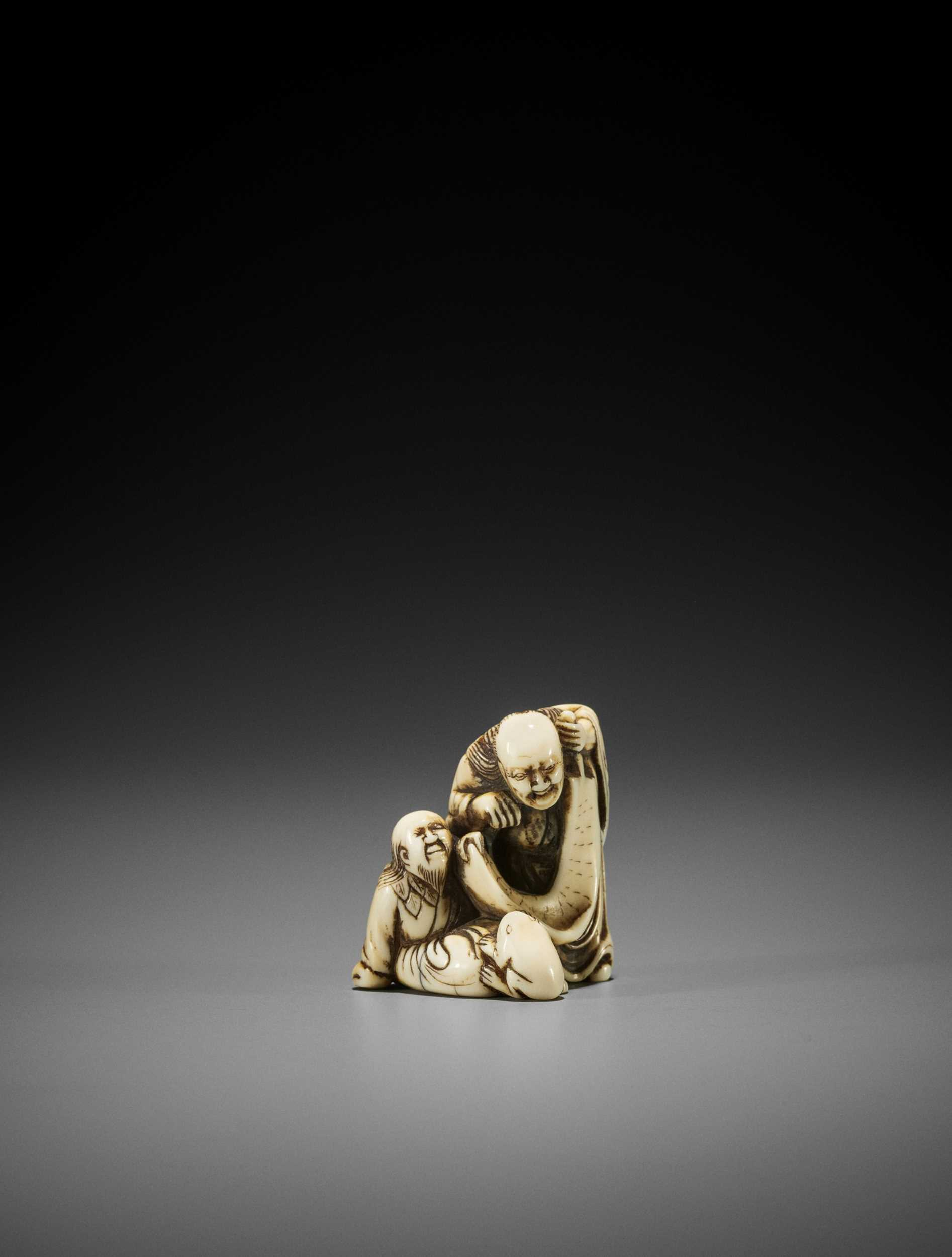 AN EARLY IVORY NETSUKE OF TWO IMMORTALS WITH SCROLL AND TOAD