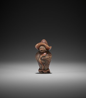 Lot 103 - MASAKATSU: A WOOD NETSUKE OF A TANUKI WRAPPED IN LOTUS LEAVES