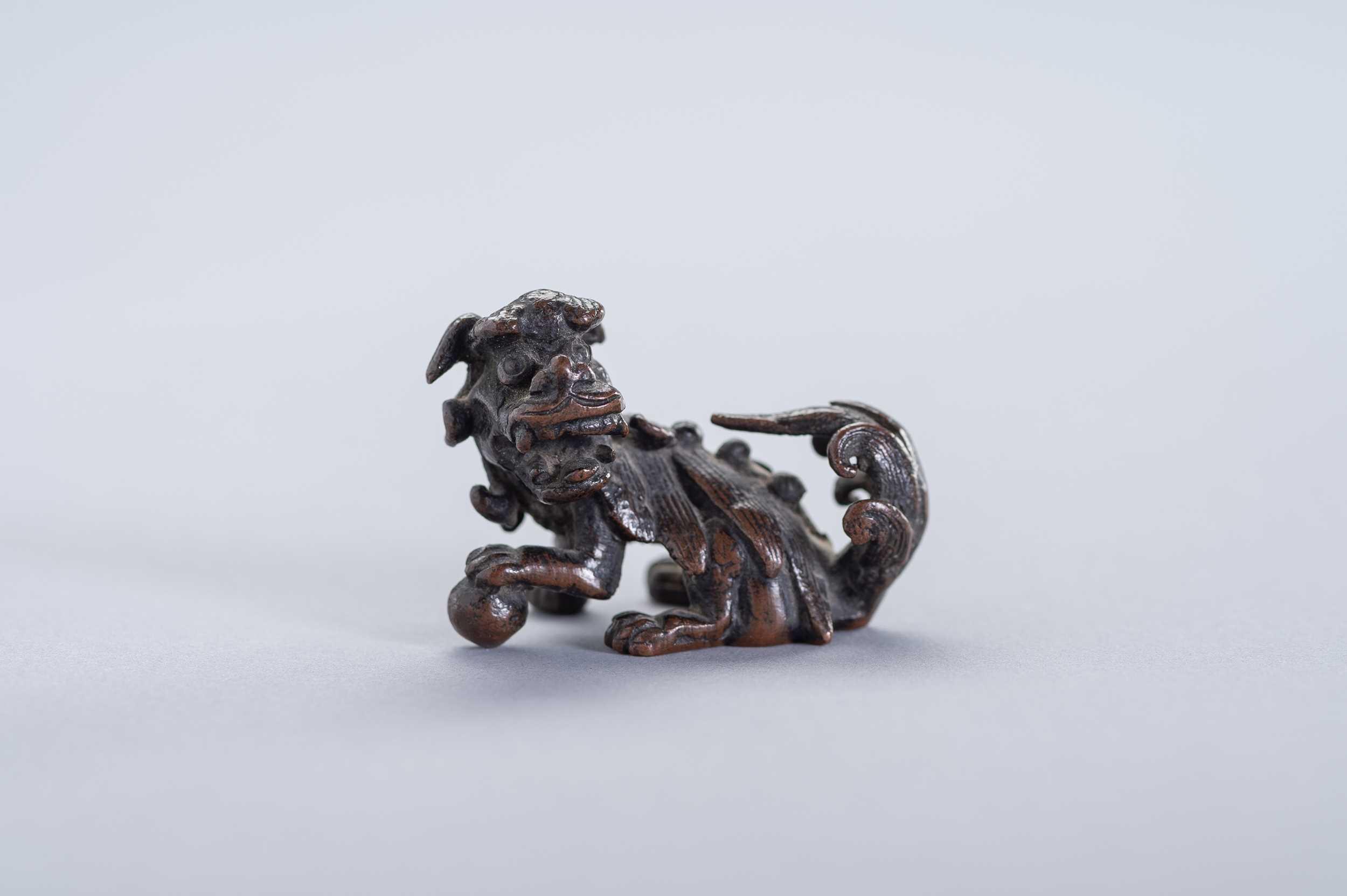 Lot 20 - A MINIATURE BRONZE FIGURE OF A BUDDHIST LION