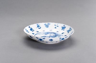 Lot 328 - A BLUE AND WHITE PORCELAIN 'GARDEN SCENE' BARBED-RIM DISH, KANGXI