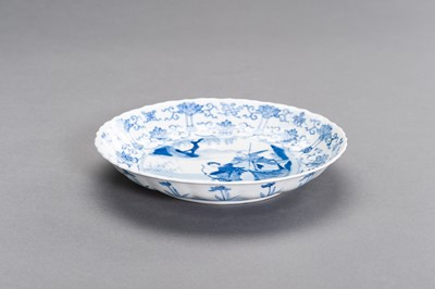 Lot 329 - A FINE BLUE AND WHITE PORCELAIN 'HUNTING PARTY' BARBED-RIM DISH, KANGXI
