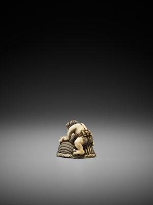 Lot 41 - OKATORI: AN IVORY NETSUKE OF AN ONI TRAPPING SHOKI
