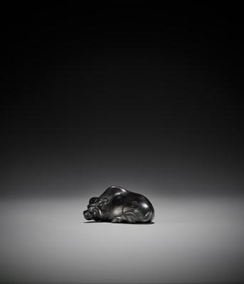 Lot 92 - MASAYOSHI: AN EBONY NETSUKE OF A RECUMBENT OX